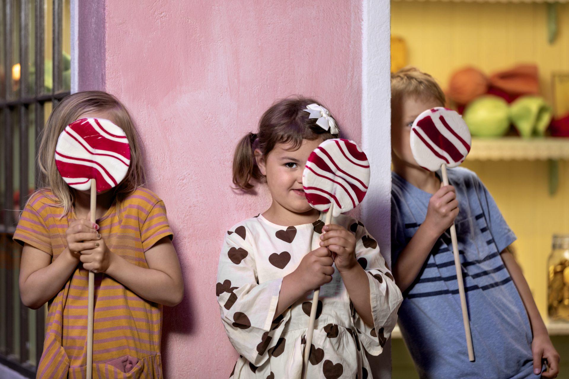 barn håller i klubbor utanför Pippis godisaffär