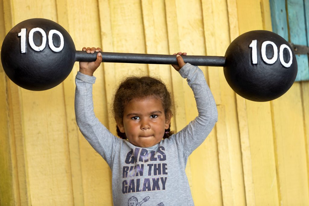 Liten flicka lyfter tunga vikter